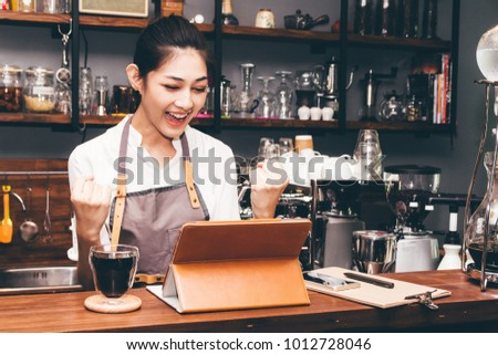 Successful woman barista celebrating with arms up at coffee shop