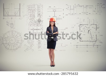 successful woman in hardhat over grey wall with prints - stock photo