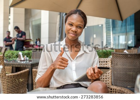 Successful woman shows thumb up. African businesswoman businessman holding a cell phone and smiling at the camera in a cafe table in Downtown Dubai - stock photo