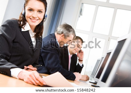 Successful woman wearing headset looking at camera on background of working men - stock photo