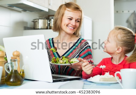 Successful woman with girl working from home using laptop - stock photo
