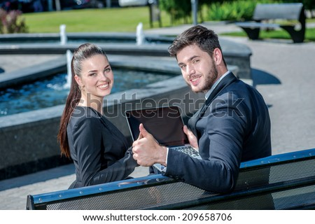 Successful work. Confident businessman and successful business woman sitting on a bench and look back and smiling at the camera. - stock photo