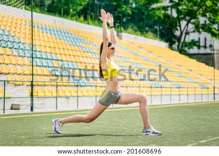 Successful workout. Woman in tracksuit makes training in the field - stock photo