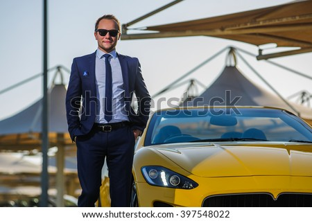 Successful yang businessman stands next to yellow cabrio car. - stock photo