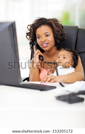successful young african american businesswoman with baby at office - stock photo