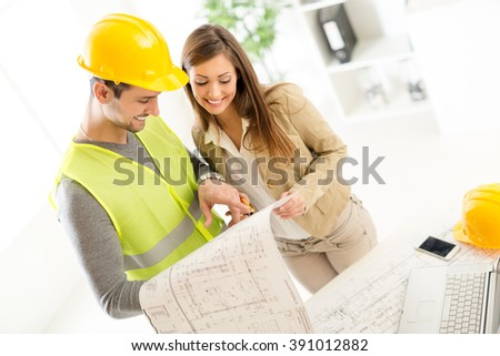 Successful young architects discussing construction plans and planning next step in office. - stock photo