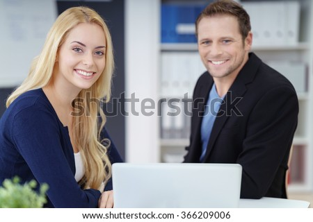 Successful young business couple working together on a self-employed business posing at a desk in their office smiling at the camera - stock photo