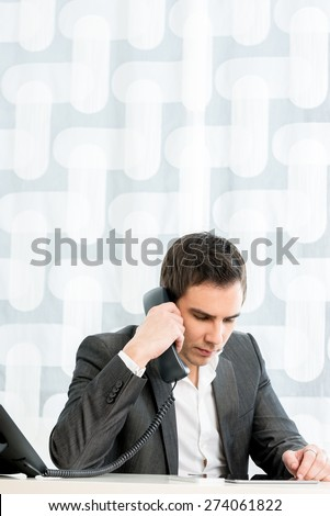 Successful young business executive talking on a phone sitting at his desk in his office as he listens to the conversation, with plenty of copyspace. - stock photo