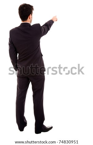 Successful young business man pointing at something interesting against white background