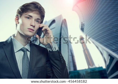 Successful young business man talking on cell phone in an urban setting - stock photo