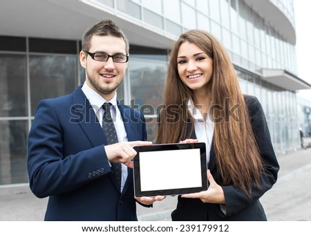 Successful young business people are holding a tablet, standing in front of his office.