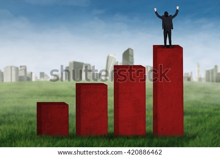 Successful young businessman expressing his success while standing on the financial chart - stock photo