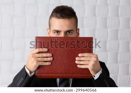 Successful young businessman hiding behind the deep red register. Short-haired man seriously carrying documents in front of him.
