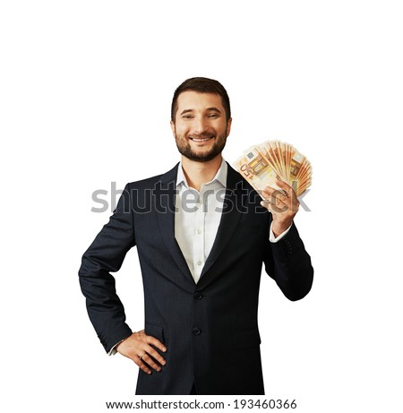 successful young businessman holding paper money and smiling. isolated on white background - stock photo