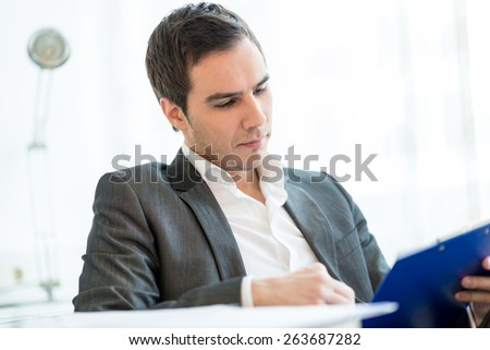 Successful  young businessman in a jacket sitting at his desk reading a report or important document with a serious expression as he analyzes the information with a white office interior behind him. - stock photo