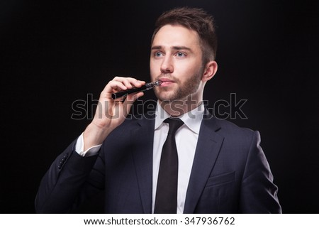 successful young businessman in a stylish business suit on a black background smoke electronic cigarette and looking at the camera.