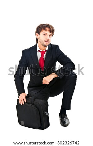 Successful young businessman kneeling full length - stock photo