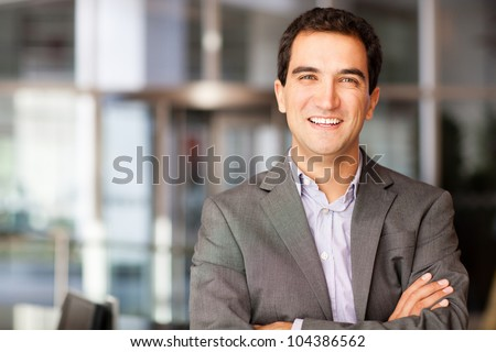 Successful young businessman with arms crossed and smiling - stock photo