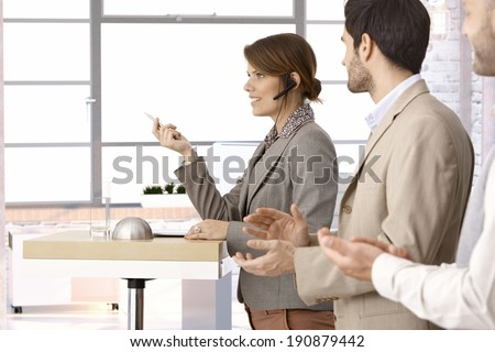 Successful young businesswoman giving presentation speech at office. People clapping, side view. - stock photo