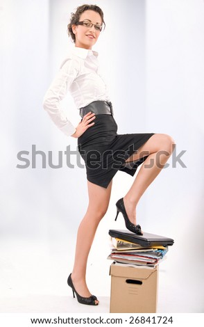 Successful young businesswoman standing on pile of documents - stock photo