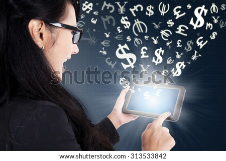 Successful young businesswoman using a digital tablet for making money online - stock photo