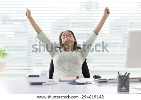 Successful young businesswoman with clenched fists at office - stock photo