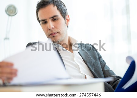 Successful young executive in a jacket sitting reading a report or document or employment application with a serious expression as he analyses the information. - stock photo