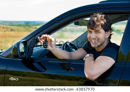 Successful young happy man showing the keys sitting in new car - stock photo