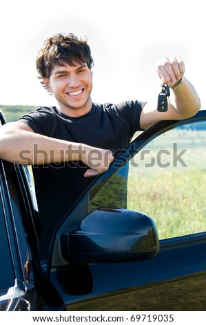 Successful young happy man showing the keys standing near the car