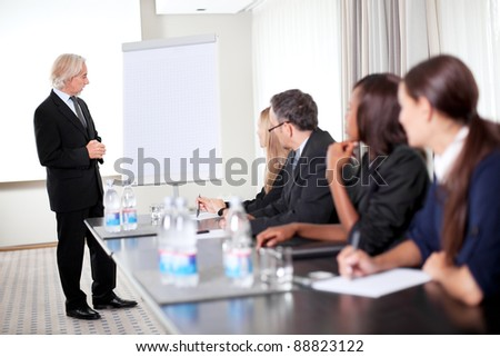 Successful young male business executive heading a business conference - stock photo