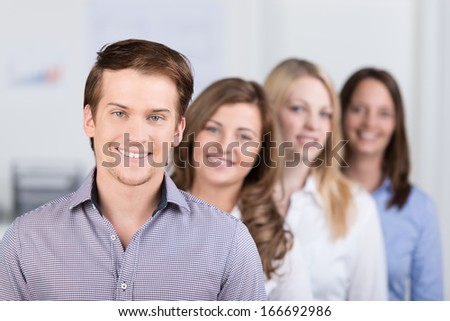 Successful young male business team leader or manager standing in front of his coworkers with a confident smile, shallow dof - stock photo