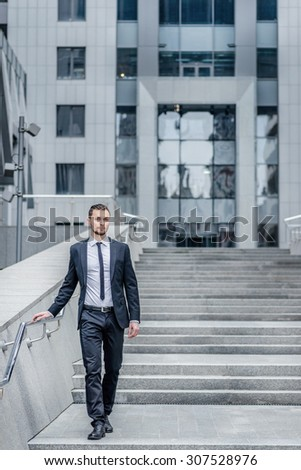 Successful young man. Confident businessman coming down the stairs to the street. Businessman dressed in formal attire and looking at the camera - stock photo