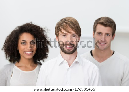Successful young multiethnic business team posing for the camera with their handsome young male leader in the foreground - stock photo