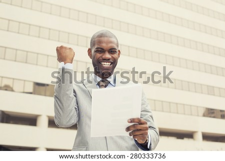 Successful young professional man celebrates success holding new contract documents. Entrepreneur enjoys success in job. - stock photo