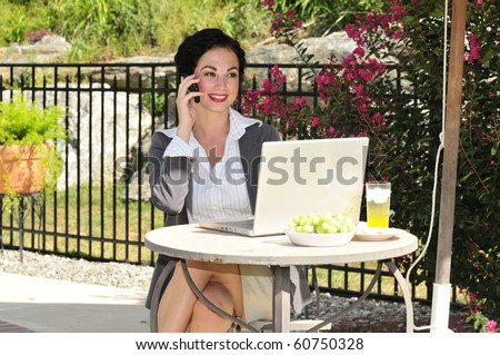 successful young woman chatting on the phone during her lunch break - stock photo