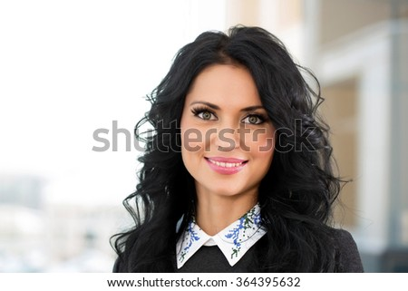 successful young woman in the office against the window does business
