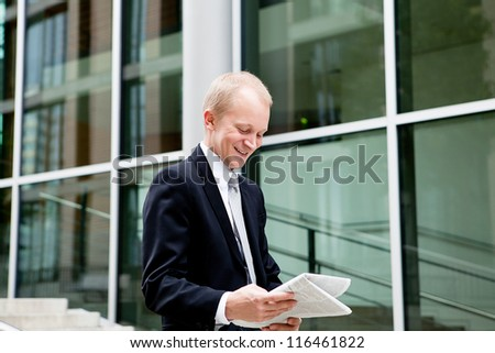 succsessful business man with tie and black dress reading newspaper