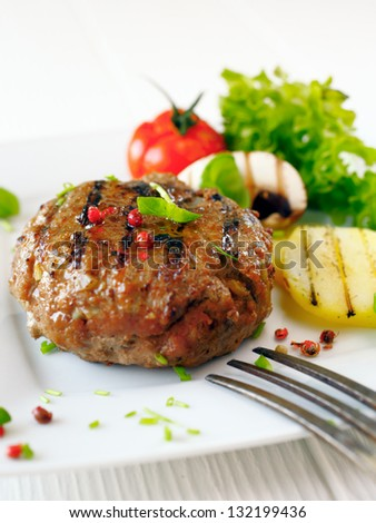 Succulent cooked beef burger with potato and salad on a white plate.