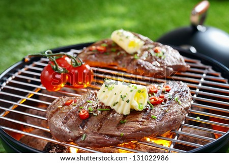Succulent portion of lean steak topped with butter and herbs grilling on a grid over hot coals in a barbecue - stock photo
