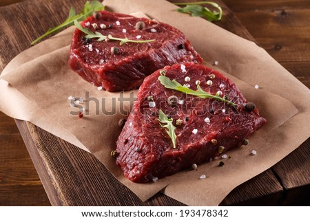 Succulent tender raw lean beef steaks lying on a sheet of oven paper in the kitchen topped with fresh herbs and spices ready to be cooked for dinner - stock photo