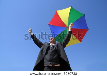 Sucess business man with coloured umbrella and arms wide open - stock photo