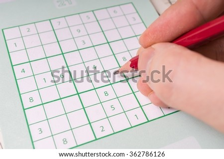Sudoku crossword and hand holding pencil is solving puzzle. - stock photo