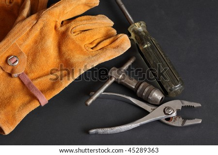 Suede leather work glove battered screw driver pliers and tap handle on a black background - stock photo