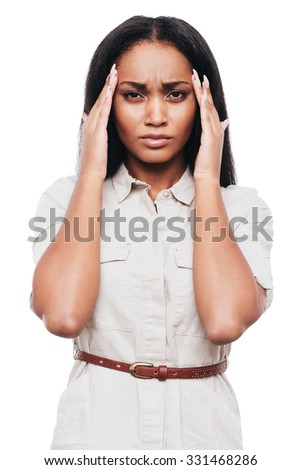 Suffering from headache. Frustrated young African woman touching her head with hands and looking at camera while standing against white background - stock photo