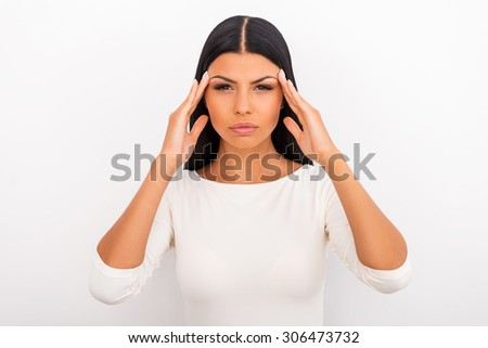 Suffering from migraine. Frustrated young woman touching her forehead and looking at camera while standing against white background - stock photo