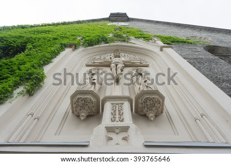 Suffering of Jesus Christ on the ancient church wall. Sculpture of the suffering of Jesus Christ , placed on the wall old Christian Church. Catholic church wall with Jesus Christ. Old white church. - stock photo