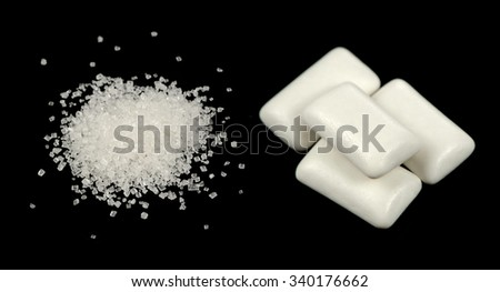 Sugar and Chewing Gum Pellets on Black Background - stock photo