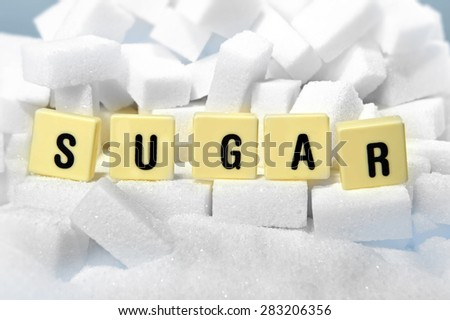 sugar block letters word on pile of sugar cubes close up in addiction , sweet nutrition , unhealthy eating and diet concept - stock photo