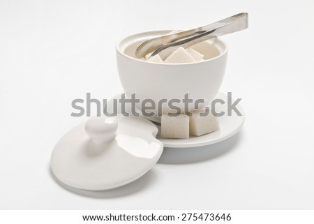sugar bowl, two cubes of sugar on a white background - stock photo