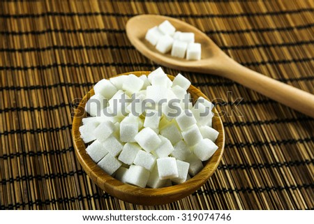 Sugar Cubes in Bowl and on Wooden Spoon over Wooden Background - stock photo